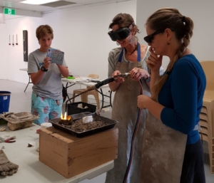 Workshop participants learning to pour molten silver into a carved cuttlebone cast.
